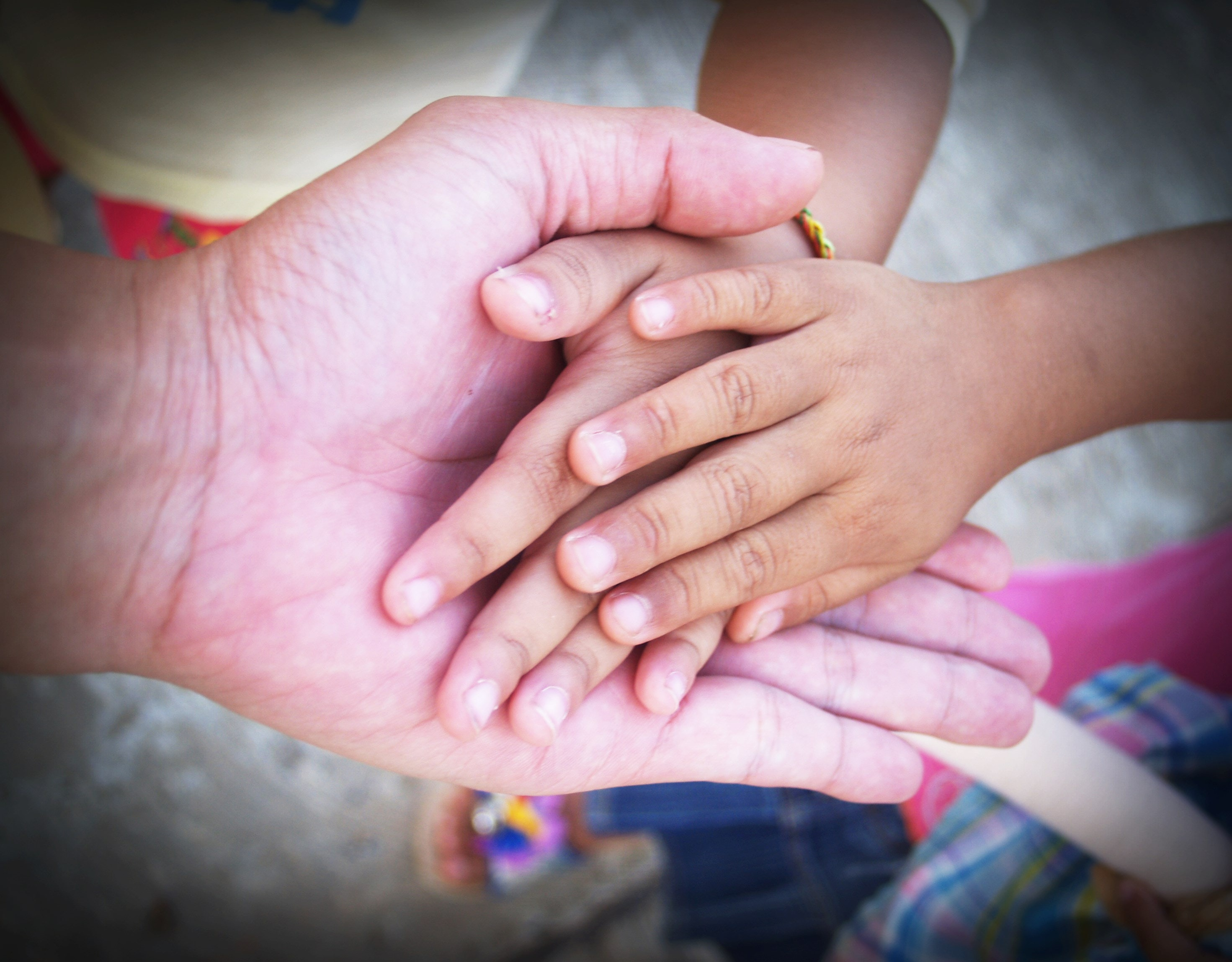 estate planning image of adult hand holding two child hands